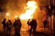 زجاجة حارقة تنفجر بجوار عناصر من شرطة مكافحة الشغب في أثينا يوم الثلاثاء. تصوير: الكيس قنسطنطنيدس - رويترز.